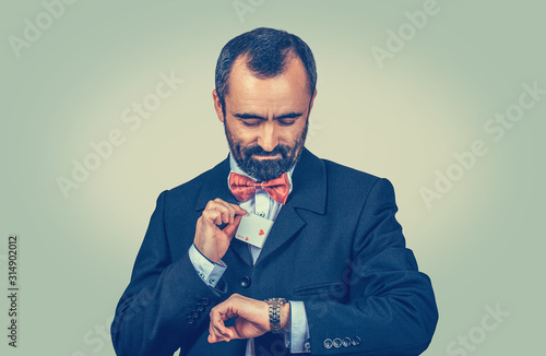 Obraz na plátne man showing a hidden ace card out of his pocket looking at his wristwatch