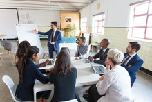 Confident Business Team Working At Office. Group Of Workers Sitting At Table And Listening Speaker. Business Meeting Concept