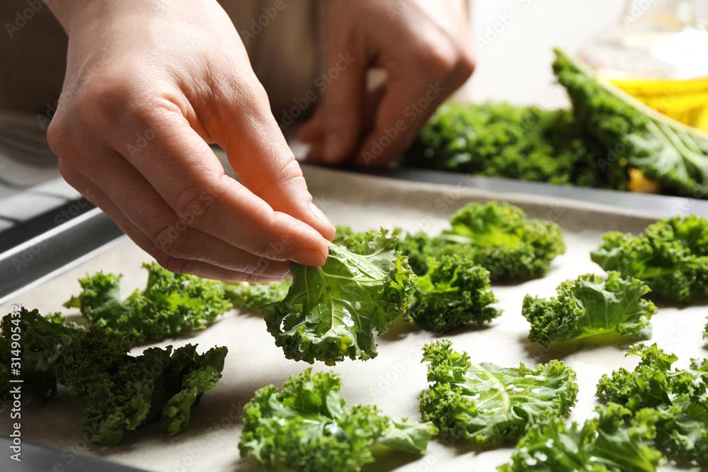 Fototapeta Woman preparing kale chips at table, closeup