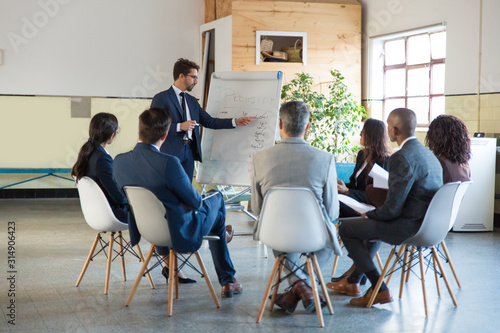 Obraz Thoughtful speaker pointing at whiteboard. Group of employees discussing ideas during presentation of new project at briefing. Business meeting concept - fototapety do salonu