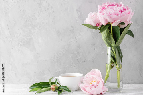 Fototapeta Festive pink peony flowers bouquet with coffee cup on white table with copy space. still life. wedding background obraz