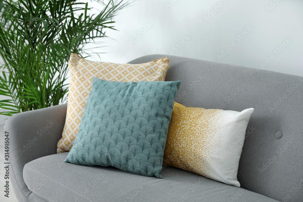 Fototapeta Different soft pillows on sofa in living room