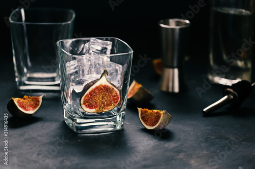 Prepares a cocktail with figs. Glass with ice. Canvas Print