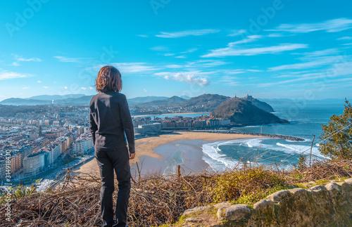 A young woman watching San Sebastian from Mount Ulia. Guipúzcoa