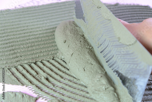 Photo Apply adhesive mortar to an xps thermal insulation board with a notched trowel