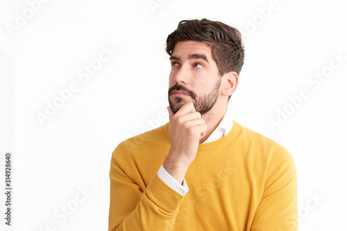 Fotomural Handsome young man looking thoughtfully at isolated white background with copy s