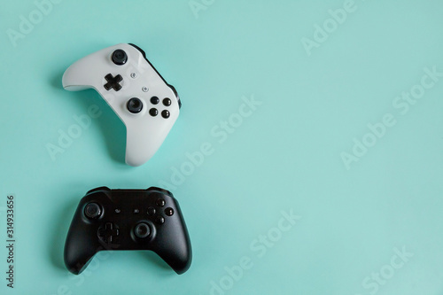 White and black two joystick gamepad, game console isolated on pastel blue colourful trendy background. Computer gaming competition videogame control confrontation concept. Cyberspace symbol.