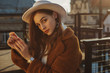 Leinwandbild Motiv Outdoor fashion portrait of young elegant fashionable brunette woman, model wearing stylish white hat, wrist watch,  brown faux fur coat, posing at sunset, in European city. Copy empty space for text