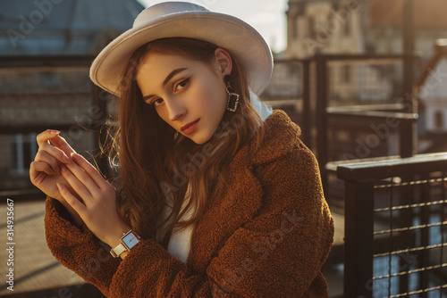 Obraz Outdoor fashion portrait of young elegant fashionable brunette woman, model wearing stylish white hat, wrist watch,  brown faux fur coat, posing at sunset, in European city. Copy empty space for text - fototapety do salonu