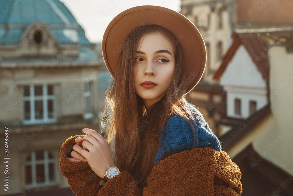 Fototapeta Elegant fashionable brunette woman, model wearing stylish hat, wrist watch, blue sweater, brown faux fur coat, posing in European city. Copy empty space for text