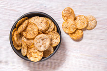 Top View Pile Of Organic, Crispy, Baked, Whole Grain Rice Chips With Spices. Gluten Free Healthy Snack. Black Ceramic Bowl On Wooden Background