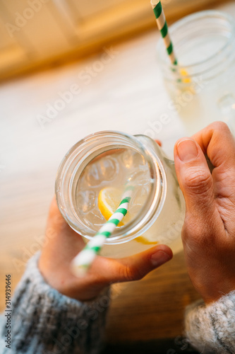 Point of view of a woman drinking homemade lemonade from a jug close to a window