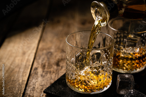 Fotografia Whiskey in glasses on wood background, copy space, toned