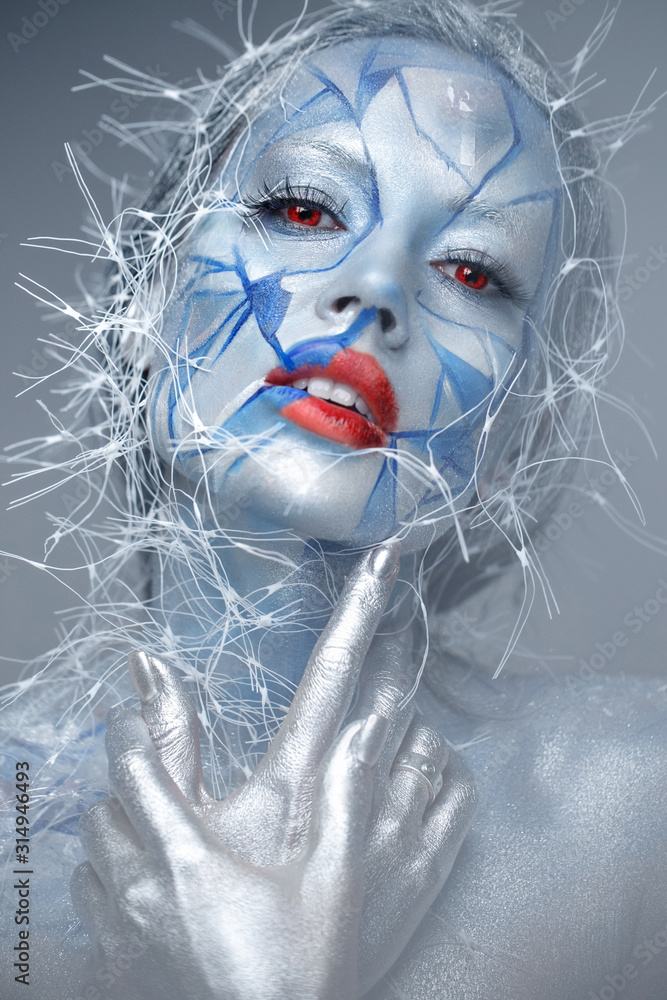 Fototapeta Beautiful girl in an unusual winter look with red lips. Creative make- up. Art look.