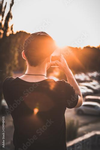 hombre con camiseta negra sacando una fotografía con su teléfono móvil al atarde Wallpaper Mural