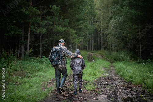 Canvas Print Hunters with hunting equipment going away through rural field towards forest at sunset during hunting season in countryside