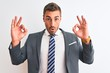 Young handsome business man wearing suit and tie over isolated background looking surprised and shocked doing ok approval symbol with fingers. Crazy expression