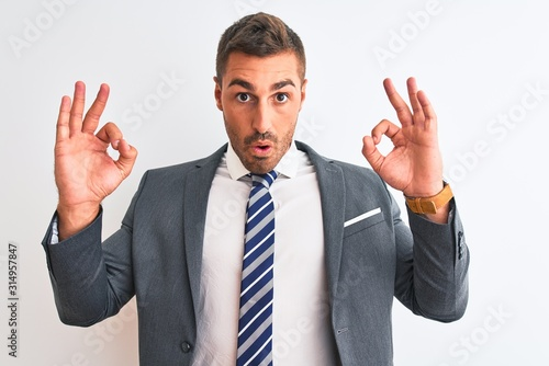 Fotomural Young handsome business man wearing suit and tie over isolated background looking surprised and shocked doing ok approval symbol with fingers