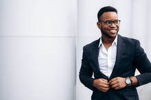 Attractive African American Businessman In Stylish Suit Is Fastens His Jacket And Smiling, Outdoors