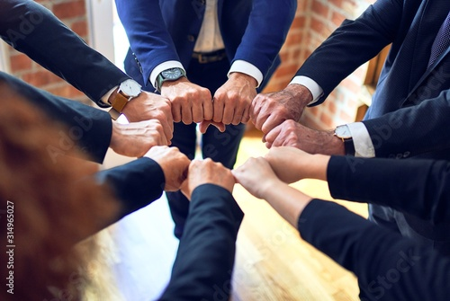 Group of business workers standing on a circle doing symbol with fists together at the office.