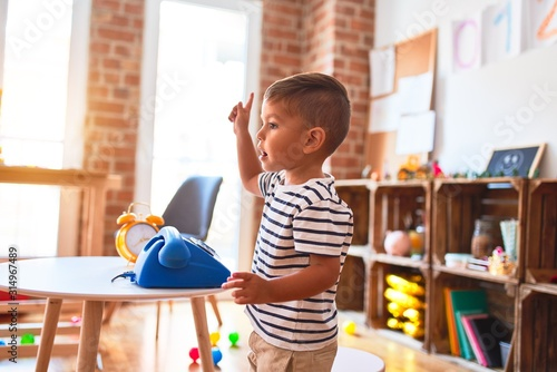 Obraz Beautiful toddler boy playing with vintage blue phone at kindergarten - fototapety do salonu