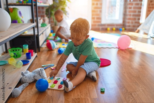 Obraz Adorable toddlers playing around lots of toys at kindergarten - fototapety do salonu