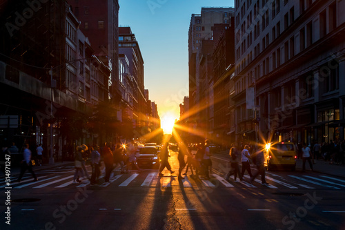 Fototapeta Crowds of diverse people walk across a busy intersection on 5th Avenue in New York City with sunlight background obraz