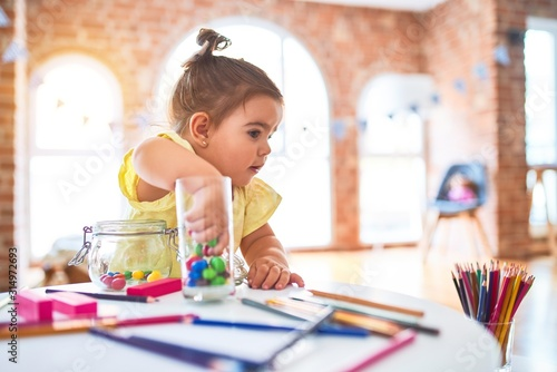 Obraz Beautiful toddler standing playing with chocolate colored balls on the table at kindergarten - fototapety do salonu