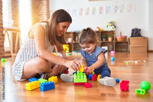 Fototapeta Young beautiful teacher and toddler playing with building blocks toy at kinderga