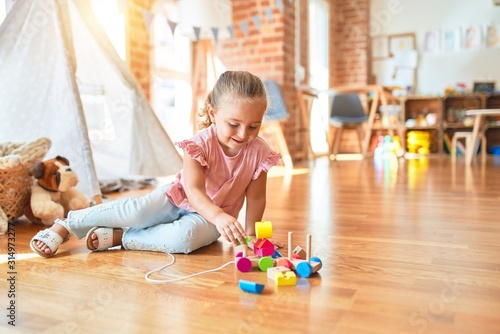 Obraz Beautiful blond toddler girl playing with train at kindergarten - fototapety do salonu
