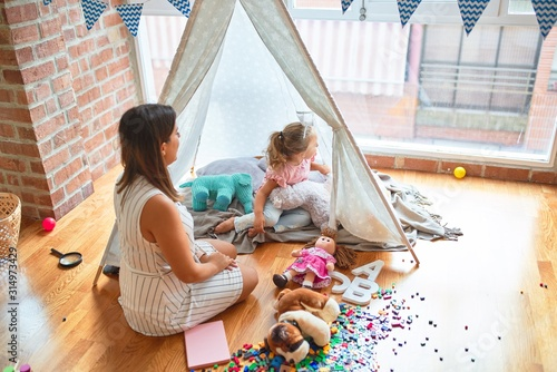 Fotomural Beautiful teacher and blond toddler girl playing with dolls inside tipi at kinde