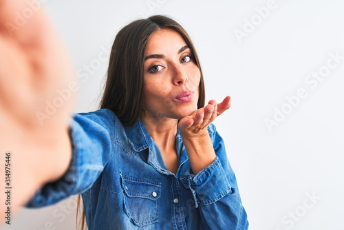 Photo Beautiful woman wearing denim shirt make selfie by camera over isolated white background looking at the camera blowing a kiss with hand on air being lovely and sexy