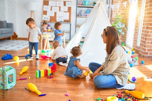 Obraz Beautiful teacher and group of toddlers playing around lots of toys at kindergarten - fototapety do salonu