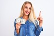 Leinwanddruck Bild - Young beautiful blond woman holding dollar standing over isolated white background surprised with an idea or question pointing finger with happy face, number one