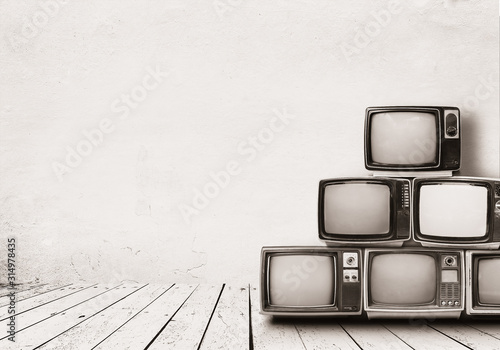 Photo Retro televisions pile on floor in old room with white wall