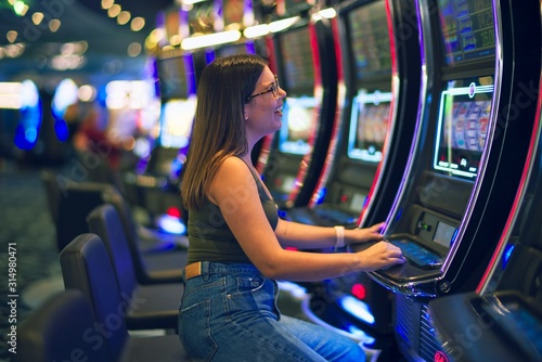 Fototapeta Young beautiful woman smiling happy and confident. Sitting with smile on face playing slot machine at casino obraz