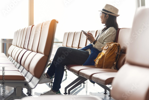 Fototapeta Happy Asian woman traveler is enjoying with smartphone. obraz
