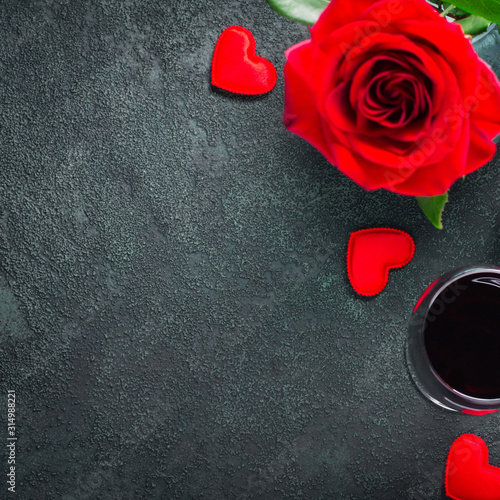 Fototapeta Valentines day or romantic meeting concept. Red rose and red wine on gray background obraz