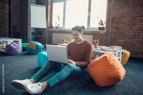 Obraz Dark-haired freelancer sitting on the floor with laptop while working - fototapety do salonu