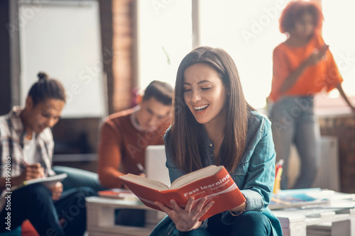 Obraz Beaming student feeling happy while studying foreign language - fototapety do salonu