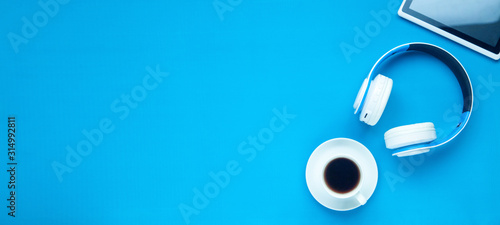 Fototapeta White wireless headphones, tablet, coffee on the blue background. obraz na płótnie
