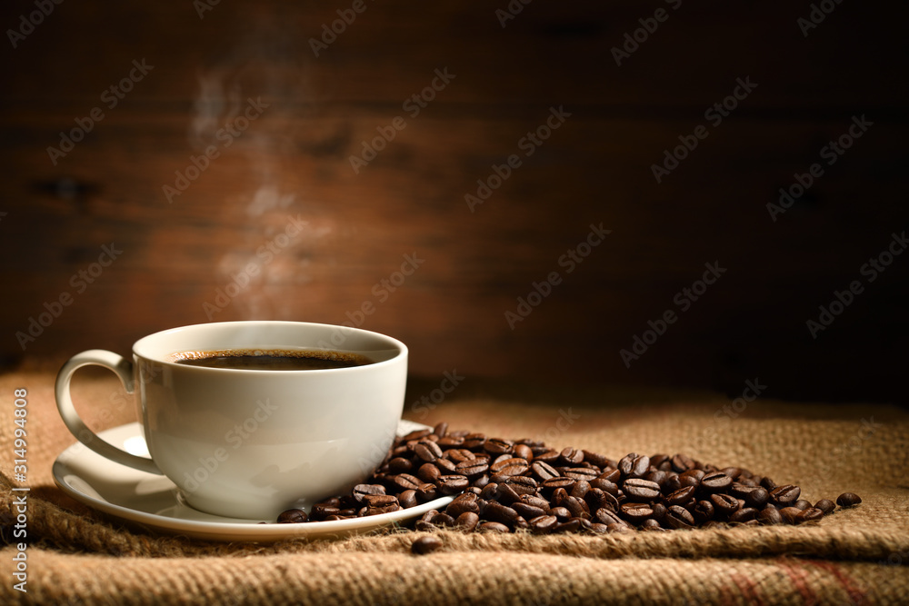 Fototapeta Cup of coffee with smoke and coffee beans on burlap sack on old wooden background