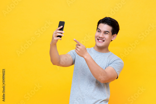 Cuadros en Lienzo Young happy Asian man selfie with smartphone