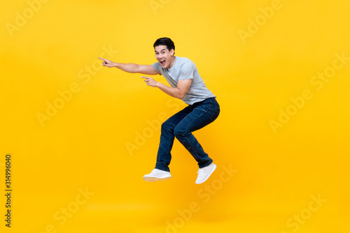 Photo Energetic excited young Asian man in casual clothes jumping in yellow background