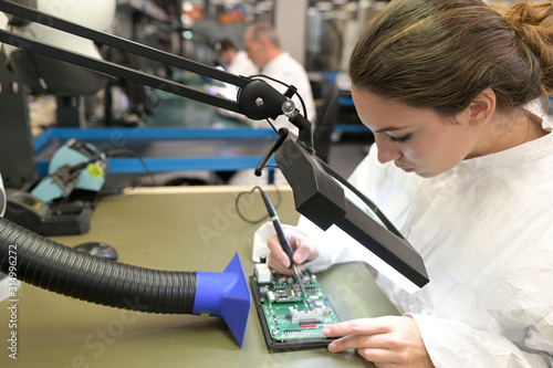 Fotografia, Obraz Young woman apprentice working in microelectronics lab