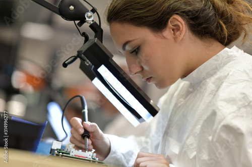 Fototapeta Young woman apprentice working in microelectronics lab