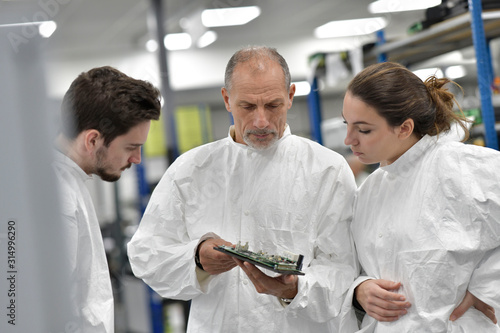Obraz na plátně Engineer with trainees in microelectronics industry
