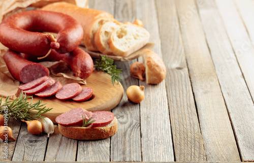Fotografiet  On a old wooden table sausage with bread, rosemary, onion and pepper