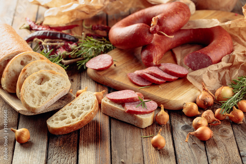 Obraz na plátně  On a old wooden table sausage with bread, rosemary, onion and pepper