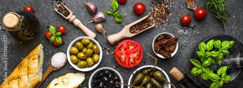 Fototapeta Mediterranean food background. Cooking ingredients on dark stone.